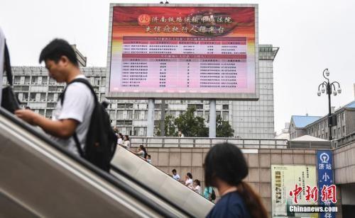 """济南火车站大屏幕曝光失信""""老赖""""。中新社记者 张勇 摄"""