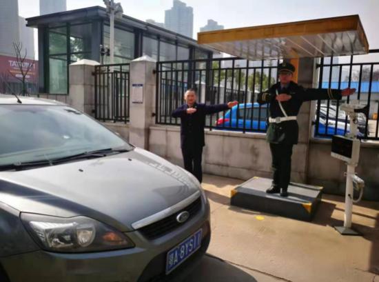 图为营业室青年员工杨庆国在单位侧门协同物业公司保安人员疏导出入车辆。 陈丽坤 摄