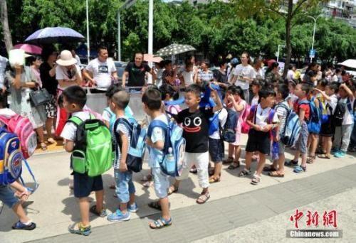 资料图:家长们在校外等候自己刚上小学一年级的小孩。张斌 摄