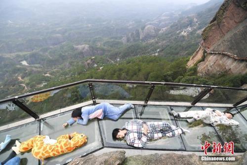 资料图:2017年3月21日,正值世界睡眠日,游人身着卡通睡衣躺在湖南平江石牛寨的悬崖玻璃栈道上,摆出各种睡姿享受睡眠,以此行为艺术呼吁关注睡眠健康。 杨华峰 摄