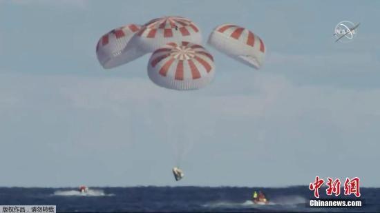 """资料图:当地时间3月8日,美国太空探索技术公司(SpaceX)的载人版""""龙""""飞船脱离国际空间站返航,成功降落在大西洋海面上。(视频截图)"""