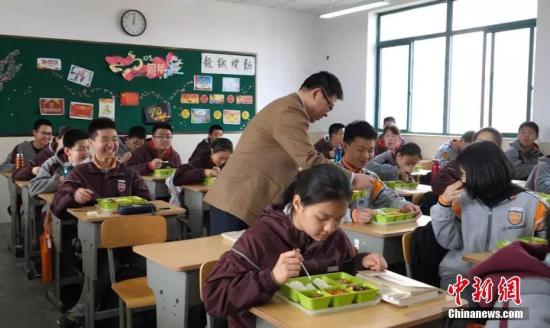 南京钟英中学的校长走进教室与学生一起吃中饭。葛勇 摄