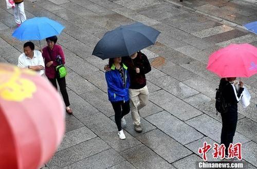 资料图:雨中的行人。中新社记者 吕明 摄