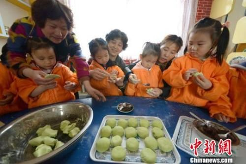 资料图:图为小朋友在老师指导下包馅做青团子。王思哲 摄