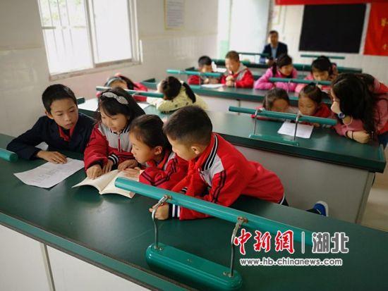 孩子们围在一起看书 谭锦涛 摄