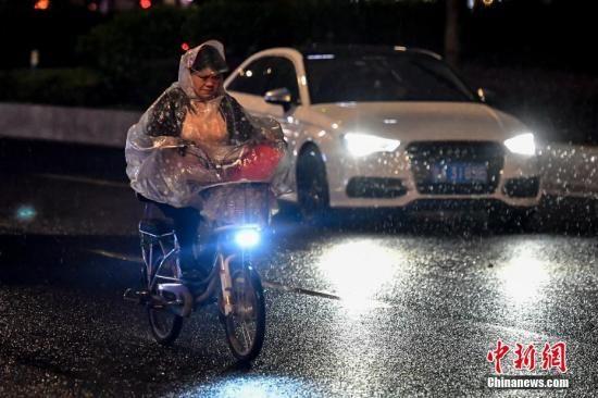 资料图:一名女子驾驶电动车行驶在雨中。中新社记者 陈骥�F 摄