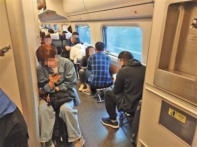 """昨日,记者乘坐D22从沈阳到北京,购买沈阳至山海关的车票体验""""买短乘长"""",补交车费和手续费后,顺利到达北京。该列车15号车厢内,有不少乘客均采用此方式乘车,因无座,不少乘客还自带折叠椅。新京报记者 潘闻博 摄"""