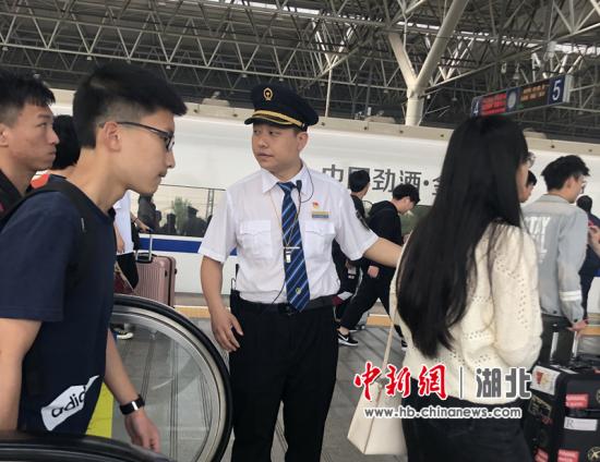 工作人员在电梯口引导旅客 陈晓燕 摄