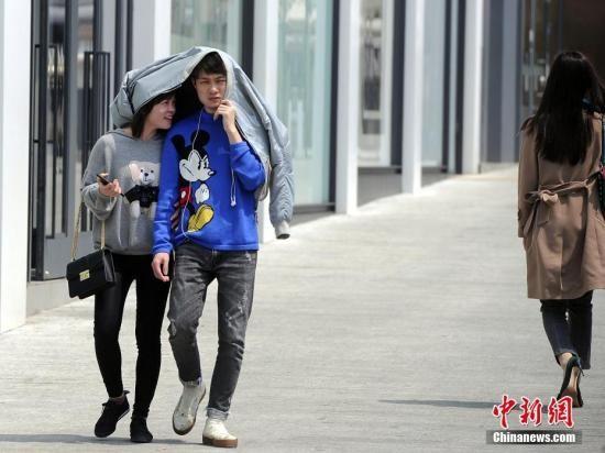 资料图:出行市民用衣物遮阳。中新社记者 蒋雪林 摄