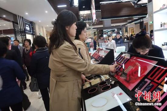 2019年4月,几名朝鲜女性在新开业的大城百货商店外国化妆品柜台前咨询。中新网 邱宇 摄