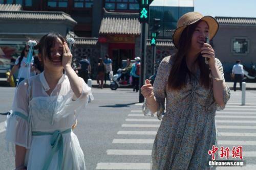 5月21日,北京天气晴晒,两位姑娘走过人行横道。 中新社记者 盛佳鹏 摄