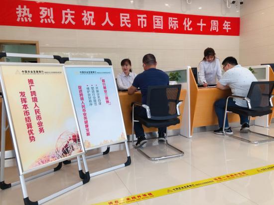 营业部国际业务部工作人员为客户办理外汇结算并推介外汇业务政策及知识 陈丽坤 摄