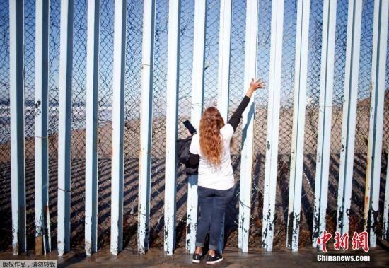 资料图:一名墨西哥女子站在美墨边境墙墨西哥一侧,向美国圣地亚哥一侧的家人打招呼。