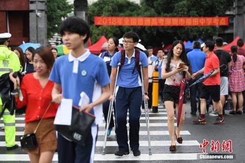 资料图:2018年6月7日,2018年高考进入第一天。图为福田中学考场外,一位高考生带伤上考场。中新社记者 陈文 摄