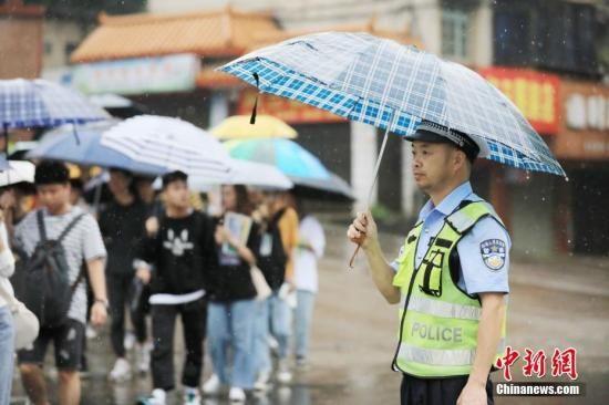 资料图:民警在风雨中坚守岗位。谭凯兴 摄
