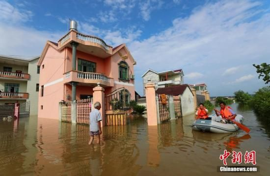 图为江西省泰和县螺溪镇镇村干部划着救生艇为灾民送矿泉水、方便面等生活用品。邓和平 摄