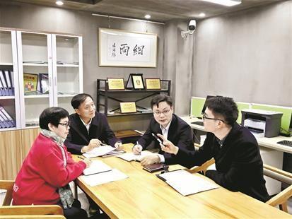 图为:李亚隆(左二)和专家志愿者研究社区戒毒问题