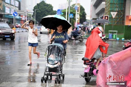 资料图:市民冒雨出行。中新社记者 俞靖 摄