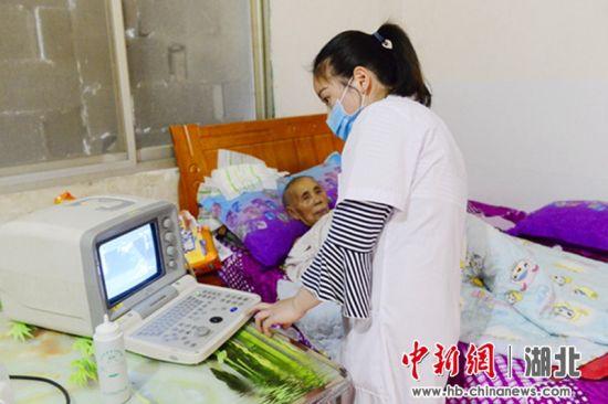 6月14日,在恩施市龙凤镇大龙潭村,村医张晓玲正在给贫困户检查身体。蔡燕 摄