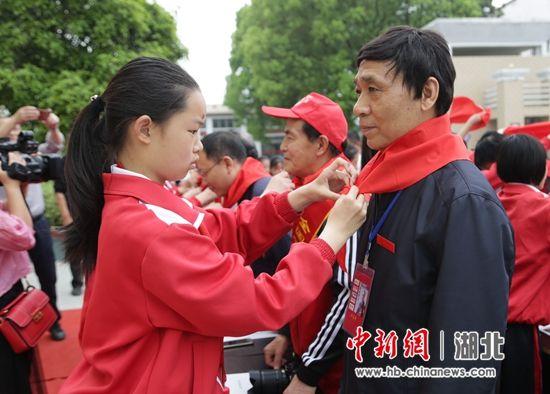 优秀少先队员为与会领导嘉宾佩戴红领巾
