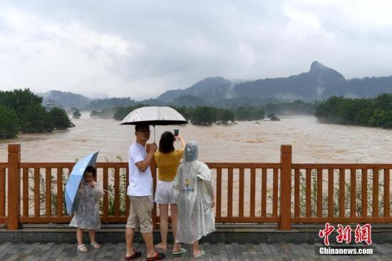7月9日,受连日来持续强降雨影响,福建武夷山河水暴涨,武夷山风景名胜区全面闭园,暂停接待游客。图为一家人在武夷山景区外一座桥上观看洪峰过境。中新社记者 王东明 摄