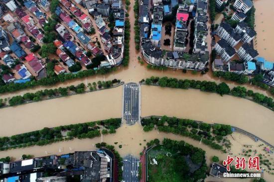 """7月9日,江西萍乡暴雨引发城市内涝 马路变""""水路""""。中新社发 胡典 摄"""