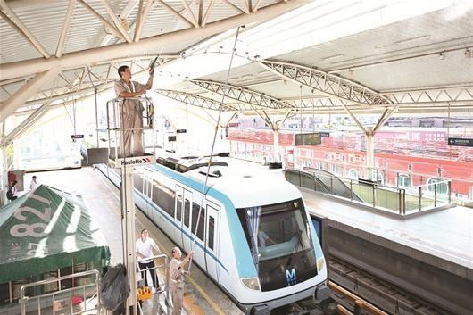 图为:工作人员正在清洁1号线车站顶棚钢结构。