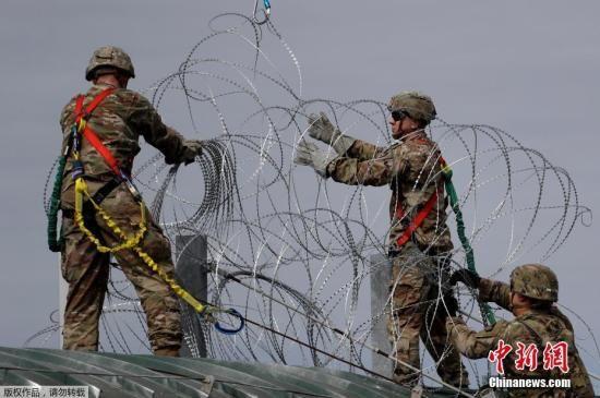 资料图:中美洲移民大军压境美国,美国士兵在美墨边境安装铁丝网严防移民入境。