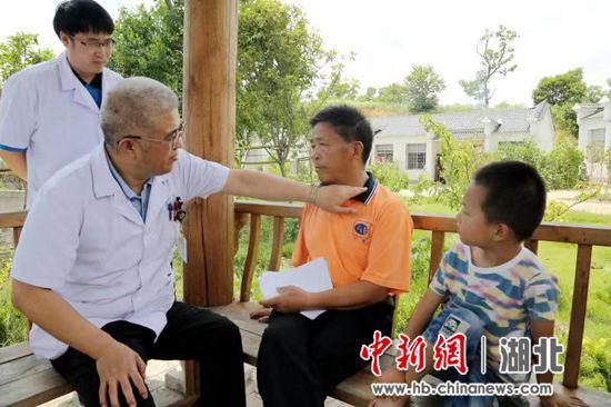 图为:现场,同济医院医生免费为村民提供医疗咨询