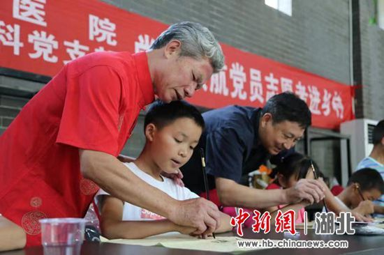 图为:百步亭书法志愿者教小朋友们写毛笔字 严鑫开 摄