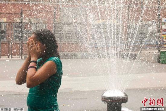 资料图:美国华盛顿,一名学生站在喷泉处纳凉。