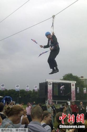 """资料图:时任伦敦市市长的鲍里斯・约翰逊为庆祝英国获得第一枚金牌而玩起""""高空飞索"""",不幸遭遇故障被悬挂半空,好几分钟上下不得。"""