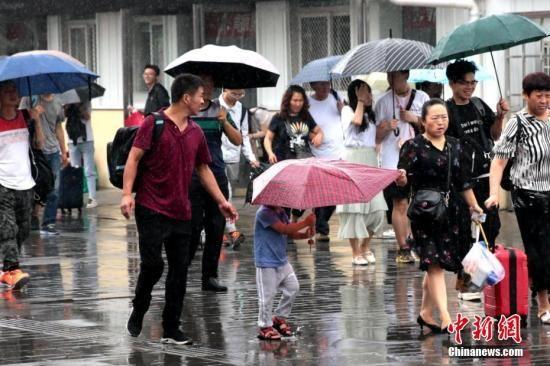 资料图:民众雨中出行。中新社记者 张远 摄