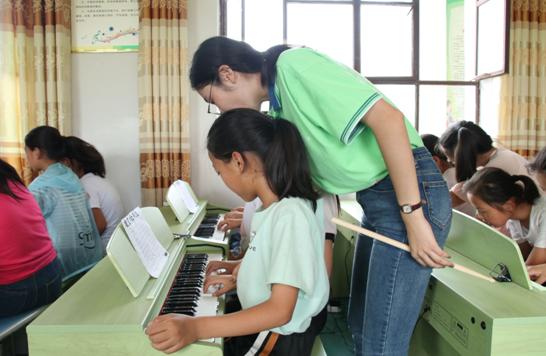 志愿者辅导学生练习钢琴