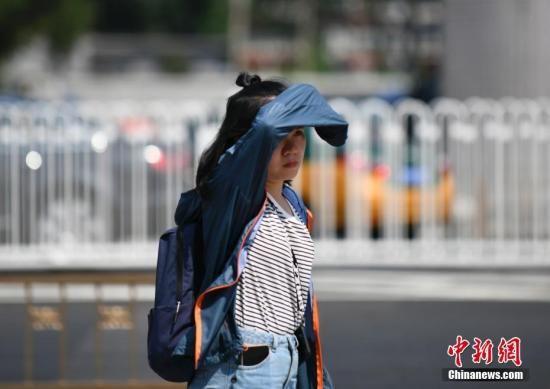 资料图:北京市民高温中出行。中新社记者 张兴龙 摄