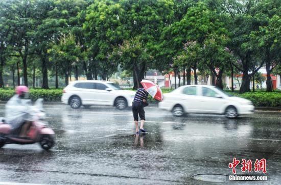 资料图:民众冒雨出行。翟李强 摄