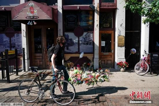 枪击案事发地的酒吧前摆满鲜花。