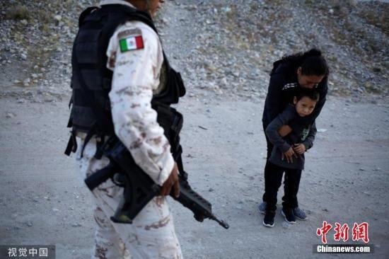 美墨边境泪目一幕:这名国民警卫队告诉移民Lety Perez,他不能让她通过,他只是在做自己的工作,而Lety Perez一再恳求。这种情况持续了几分钟,突然Lety Perez拉着儿子跑了,进入干涸的河堤,走到中间,在那里这名守卫已经没有管辖权了。图片来源:视觉中国