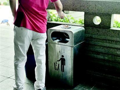 图为湖北省博物馆的垃圾桶旁,一游客正在丢烟头