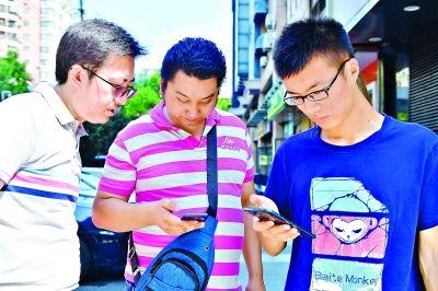 12日,邹先生(中)带着新买的5G手机,来到京汉大道单洞三路路口,在技术人员的帮助下现场体验联通5G网络