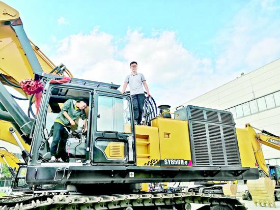 图为:地大学生韩磊和他研发的挖掘机
