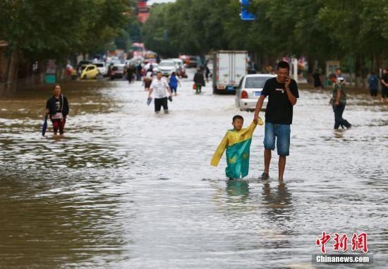 民众在积水中行走。中新社发 钟欣 摄