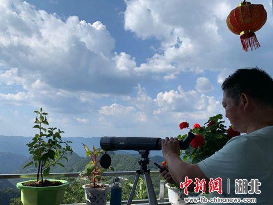 刘家荒村民宿老板谭克明在调试望远镜 便于客人观景 姚祯发摄