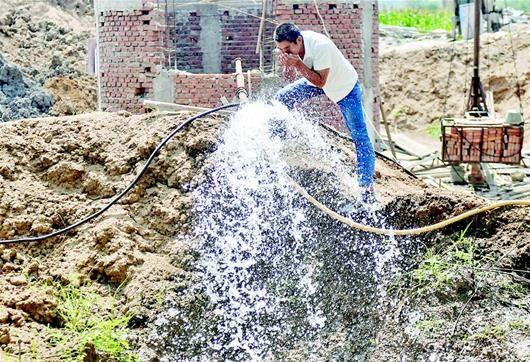 图为水从深井抽出,村民如饮甘霖