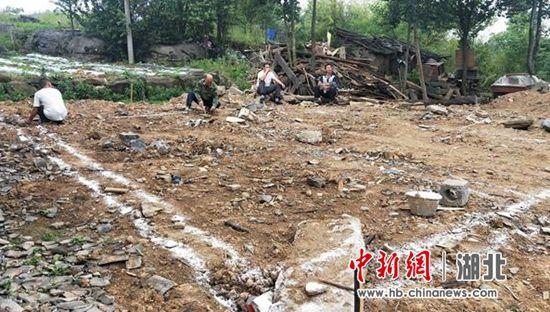 驻村工作队在帮助吴喜根选址放线砌地基