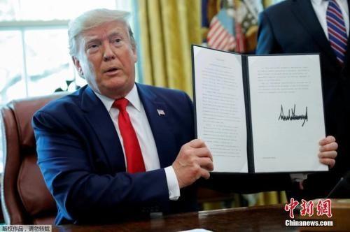 资料图:特朗普在白宫椭圆形办公室展示签署的行政令。