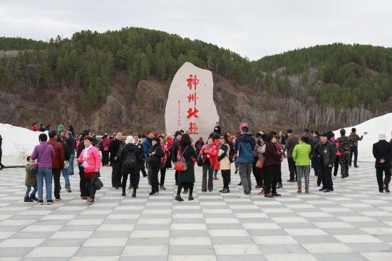 游客在漠河北极村合影留念。