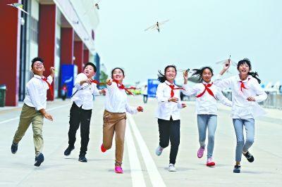 开发区青少年放飞纸飞机,期盼军运到来
