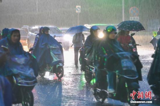 资料图为民众冒雨出行。中新社记者 骆云飞 摄