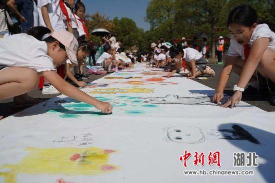 小朋友正在画卷上画画 杨锡晨 摄
